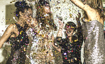 Four women wearing cocktail dresses dancing in a shower of confetti. - MINF06662