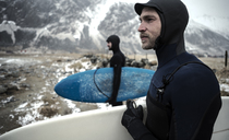 Two surfers wearing wetsuits and carrying surfboards standing on a beach with mountains behind. - MINF06668