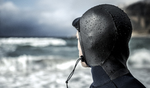 Rear view of the head of a surfer wearing a wetsuit looking out to sea. - MINF06671