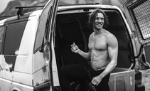 Young man standing by the open doors of a van wearing a wetsuit. - MINF06677