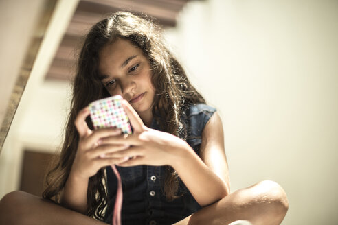 Low angle shot of a girl looking at a mobile phone screen. - MINF06680