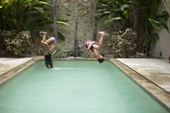 Two children in mid air, somersaulting backwards into a swimming pool. - MINF06683