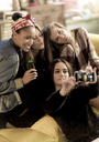 Four young women sitting on a sofa, smiling, taking a selfie, holding beer bottles. - MINF06713