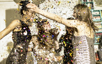 Group of young women celebrating at a party in a haze of falling glitter confetti. - MINF06722