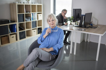 Senior businesswoman sitting in office with colleague working behind her - AWF00179