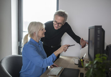 Two senior colleagues working together at desk in office - AWF00182