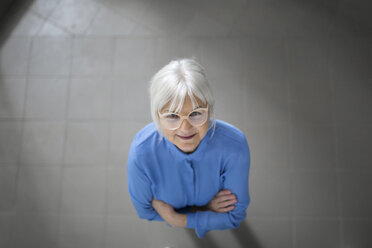 Smiling senior businesswoman looking up on office hallway - AWF00194