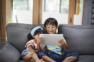 Boy and young girl with black hair sitting on a grey sofa, looking at digital tablet. - MINF06829