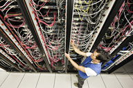 Caucasian male technician working on a CAT 5 cable bundling system in a large computer server room. - MINF06883