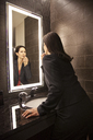 Caucasian businesswoman doing makeup in a mirror. - MINF06901