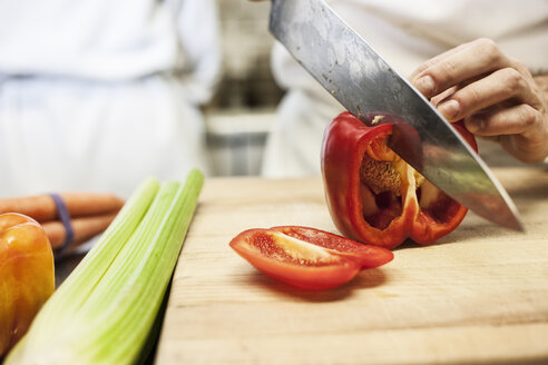 Close-up of a chef using a knife to chop vegetables. - MINF06904