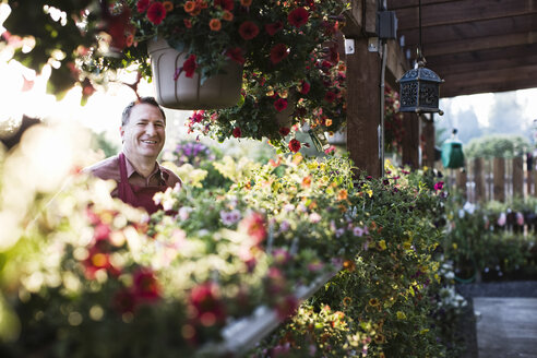 Caucasian man, a garden centre business owner standing among flowering plants in early summer. - MINF06910