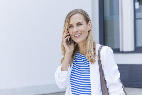 Smiling blond businesswoman using smartphone - TCF05533