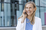 Smiling blond businesswoman using smartphone - TCF05536