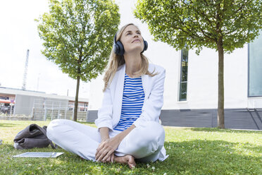 Smiling blond businesswoman sitting on meadow, listening music - TCF05542