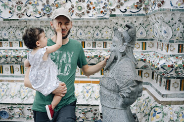 Thailand, Bangkok, Wat Arun, Father and mischievous daughter visiting the Buddhist temple - GEM02248