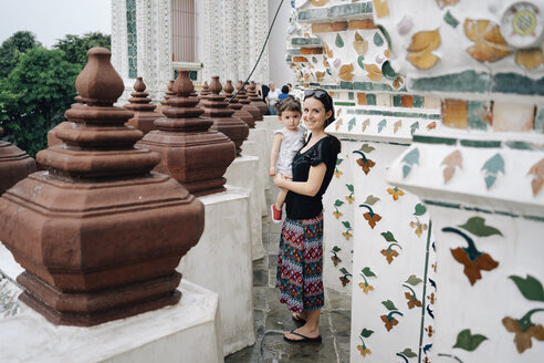 Thailand, Bangkok, Wat Arun, Portrait of smiling mother and daughter visiting the Buddhist temple - GEM02251