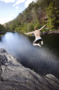Young man jumps off rock cliffs into a lagoon at High Falls Park, Geraldine, Alabama. - AURF00068