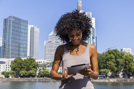 Germany, Frankfurt, smiling young woman with curly hair using tablet in the city - TCF05566