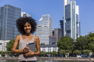 Germany, Frankfurt, portrait of smiling young woman with digital tablet in the city - TCF05569