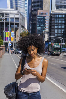 Germany, Frankfurt, smiling young woman with curly hair using cell phone - TCF05575