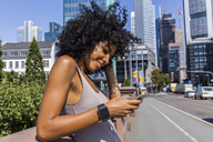 Germany, Frankfurt, portrait of smiling young woman with curly hair using cell phone in the city - TCF05578