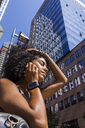 Germany, Frankfurt, portrait of young woman with smartwatch on the phone in front of skyscrapers - TCF05581