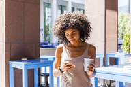 Smiling young woman with coffee to go looking at cell phone - TCF05593