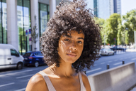 Germany, Frankfurt, portrait of young woman with curly hair - TCF05602