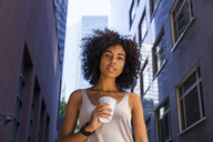Germany, Frankfurt, portrait of young woman with coffee to go in the city - TCF05605