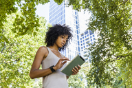 Germany, Frankfurt, young woman using tablet in the city - TCF05608