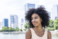 Germany, Frankfurt, portrait of smiling young woman with curly hair in front of Main River - TCF05629