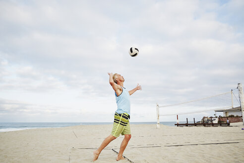 Mature man standing on a beach, playing beach volleyball. - MINF07216