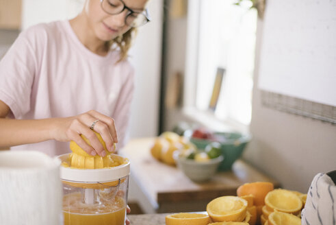 Family preparing breakfast in a kitchen, girl squeezing oranges. - MINF07420