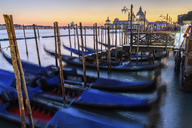 Gondolas moored on a canal in Venice, Italy, at sunrise. - MINF07486