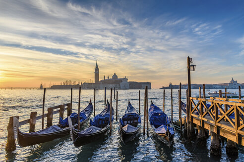 Gondolas moored on a canal in Venice, Italy, at sunrise. - MINF07489