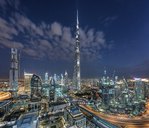 Cityscape of Dubai, United Arab Emirates at dusk, with the Burj Khalifa skyscraper and illuminated buildings in the centre. - MINF07525