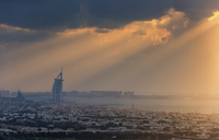 Cityscape of Dubai, United Arab Emirates at dusk with the Burj Al Arab skyscraper in the distance. - MINF07573