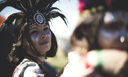 Young woman at a summer music festival face painted, wearing feather headdress, looking at camera. - MINF07624