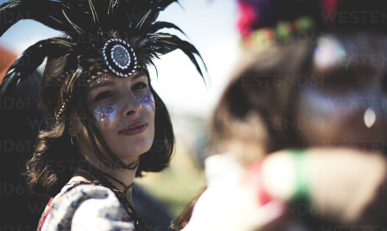 Young woman at a summer music festival face painted, wearing feather headdress, looking at camera. - MINF07624 - Mint Images/Westend61