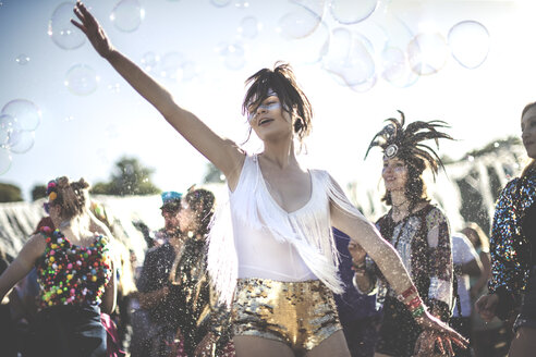 Young woman at a summer music festival wearing golden sequinned hot pants, dancing among the crowd. - MINF07633