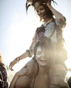 Young woman at a summer music festival carrying a friend on her shoulders, face painted, smiling at camera. - MINF07639