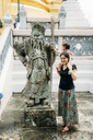 Thailand, Bangkok, portrait of smiling mother and daughter at a statue in the Grand Palace - GEM02278