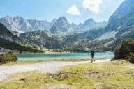 Austria, Tyrol, Man hiking at Seebensee Lake - DIGF04734