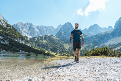 Austria, Tyrol, Man hiking at Seebensee Lake - DIGF04737