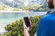 Austria, Tyrol, Hiker using compass app at Lake Seebensee - DIGF04755