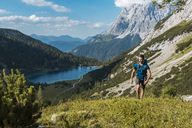 Austria, Tyrol, Young man hiking in the maountains at Lake Seebensee - DIGF04761