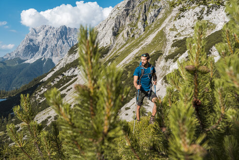 Austria, Tyrol, Young man hiking in the maountains at Lake Seebensee - DIGF04764