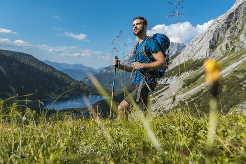 Austria, Tyrol, Young man hiking in the maountains at Lake Seebensee - DIGF04767