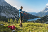 Austria, Tyrol, Hiker setting up his tent in the mountains at Lake Seebensee - DIGF04776